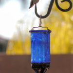 Hummingbird perched on feeder support