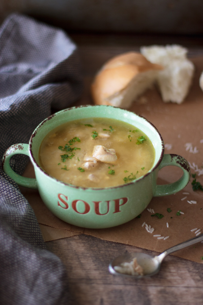 Chicken and rice soup in a bowl, featured with a spoon and bread