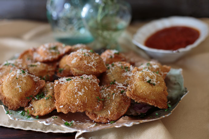 Fried ravioli stacked on a dish