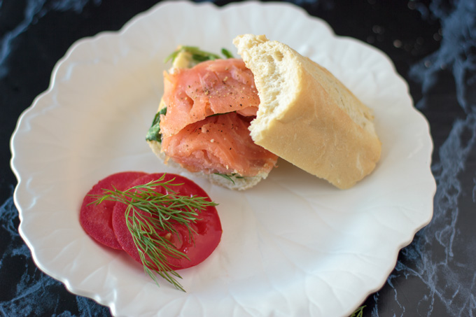Smoked salmon baguette on a plate with garnish