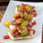 Feature image of baked cod with tapenade and warm tomato salad on a serving dish