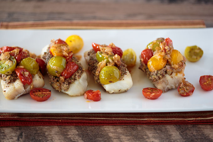 Baked cod with tapenade and warm tomato salad served
