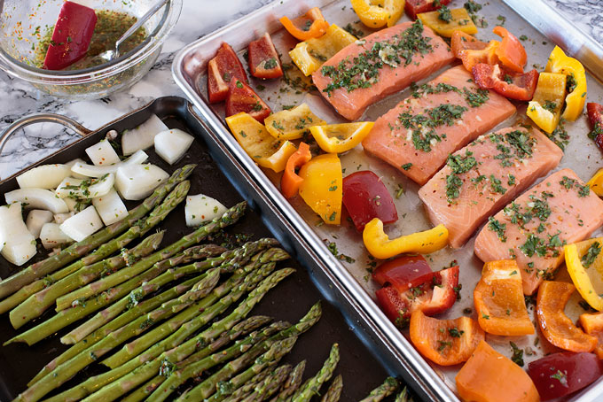 Salmon, peppers, asparagus, and onions on sheet pans with chili lime honey sauce