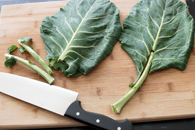 Removing the stems from the collard green leaves