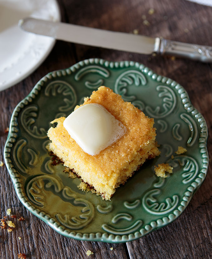 Sweet cornbread piece on a plate topped with melted butter