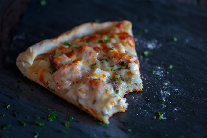 Slice of salmon and herb pizza with bites taken out