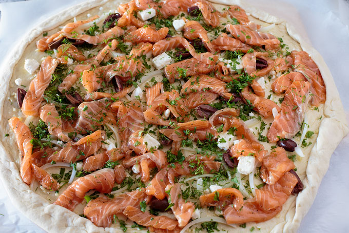 Salmon and herb pizza with toppings before cheese