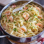 Shrimp scampi with linguini in the pan with serving tongs