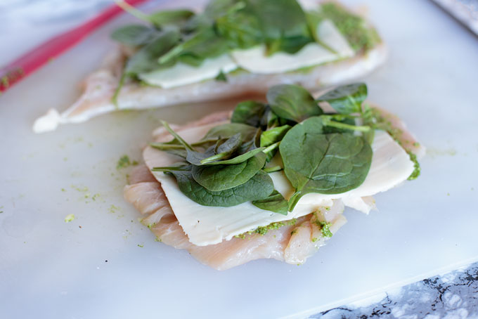 Raw pounded chicken breast with pesto, Havarti, and spinach before rolling