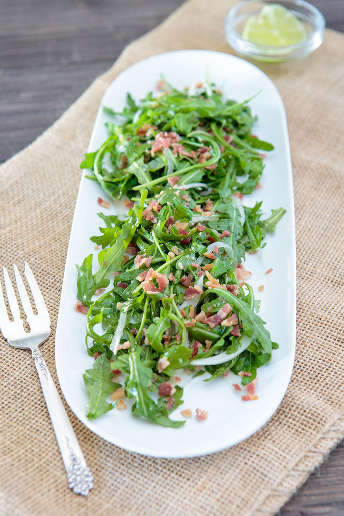 Wilted arugula and bacon salad on a plate