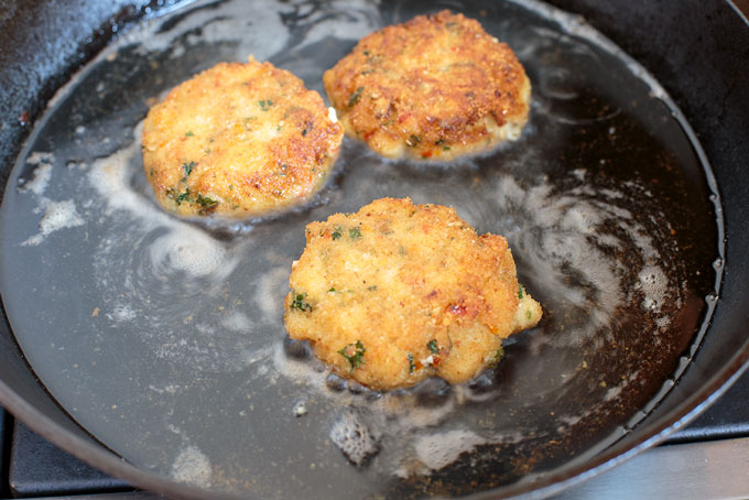 Fish cakes frying in oil in a skillet