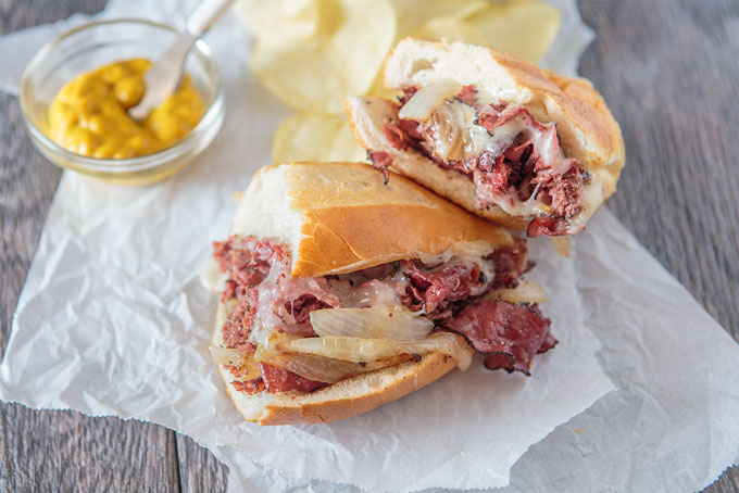 Two halves of the grilled pastrami and provolone