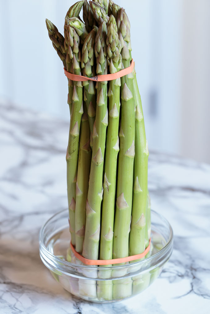 Asparagus in a small bowl with water