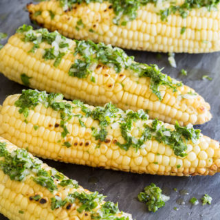 Prepared grilled corn with herbs on a slate, portrait orientation