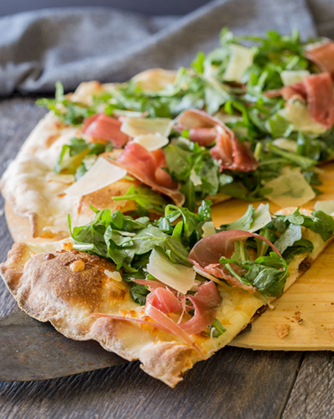 Prosciutto and arugula pizza, sliced
