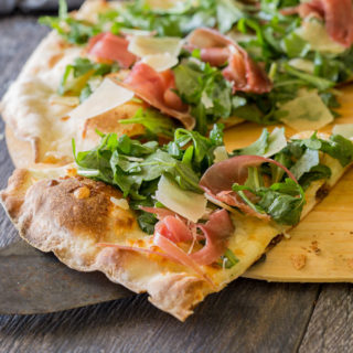 Prosciutto and arugula pizza , sliced