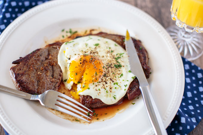 Steak and egg on a plate cut with fork and knife