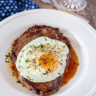 Steak and egg on a plate garnished with parsley, portrait orientation