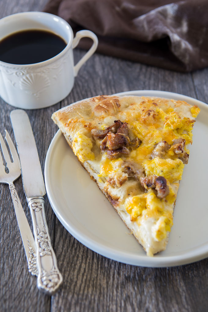 Slice of sausage breakfast pizza on a plate