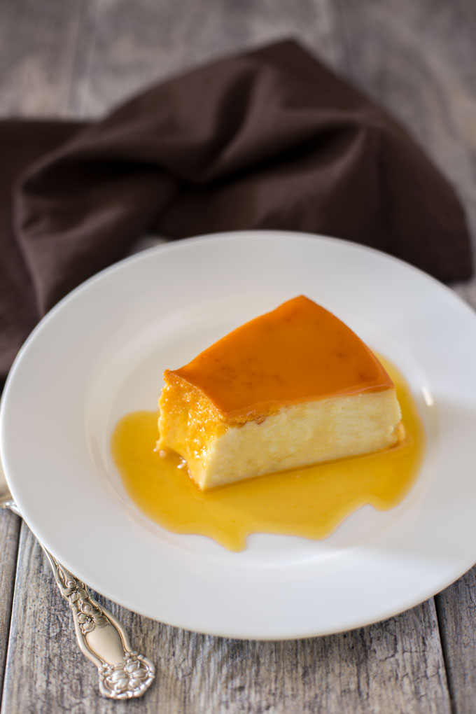 A wedge of flan on a plate covered with caramel sauce