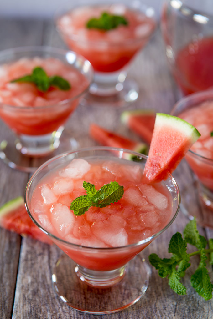 Watermelon cocktail in a glass with ice, garnished with a wedge of watermelon and mint