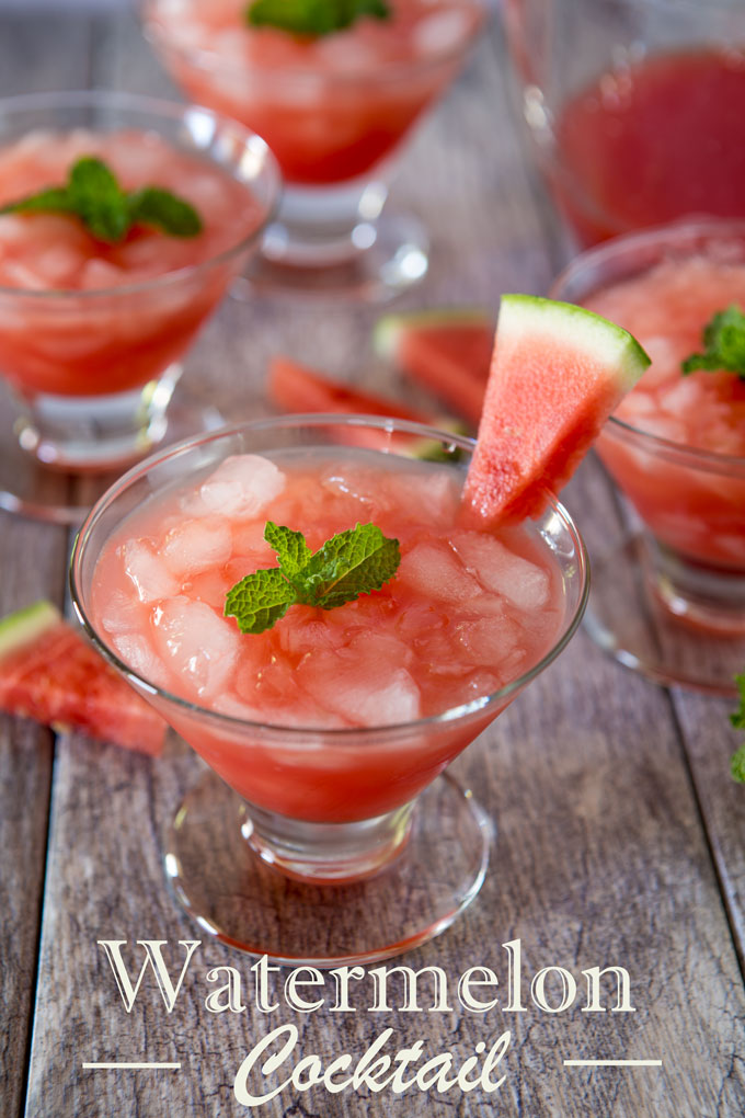 Watermelon cocktail in a glass with ice, garnished with a wedge of watermelon and mint with a text banner