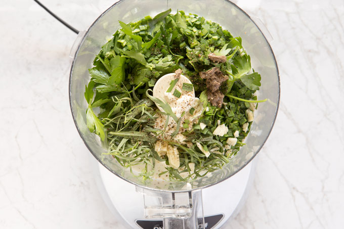 Green goddess dressing ingredients in a food processor