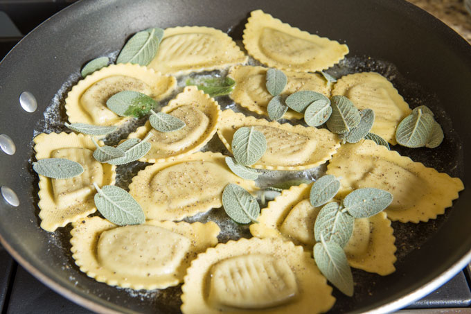 Agnolotti in melted butter in the pan with sage leaves