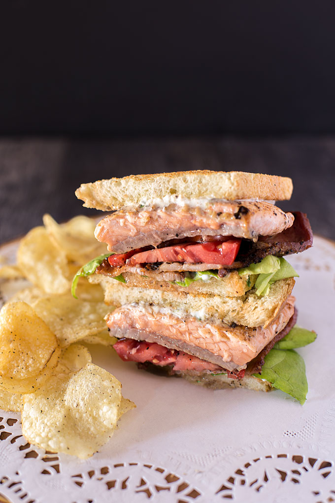 Salmon BLT sandwich halves stacked, with chips