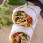 Finished turkey fajita wraps, wrapped in paper and stacked on a cutting board