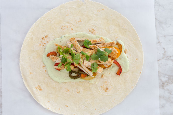 Layering the filling for the turkey fajita wraps on the tortilla