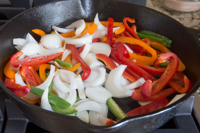 Grilling the peppers and onions in a cast iron pan