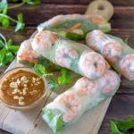 Shrimp spring rolls on a cutting board, with mint sprigs and peanut dipping sauce