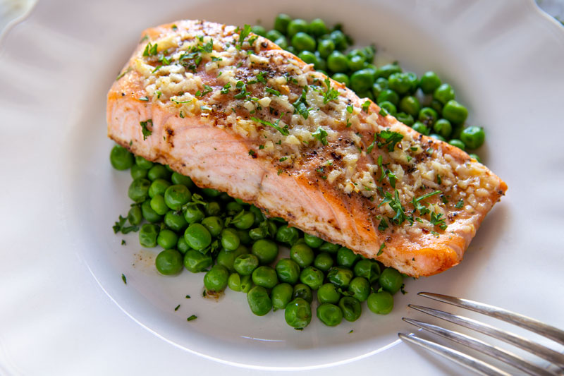 Baked salmon scampi on a bed of peas, close up shot
