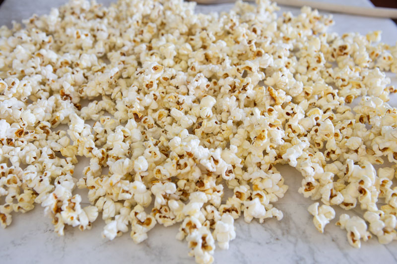 spreading the cooked kettle corn over parchment paper to cool