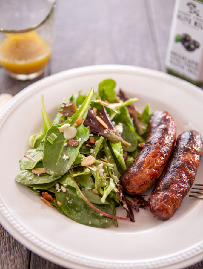 Nut 'n' honey salad with Itaian sausageon a table with dressing and olive oil on the side