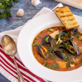 Feature image of plated cioppino in a bowl with grilled sourdough crostini