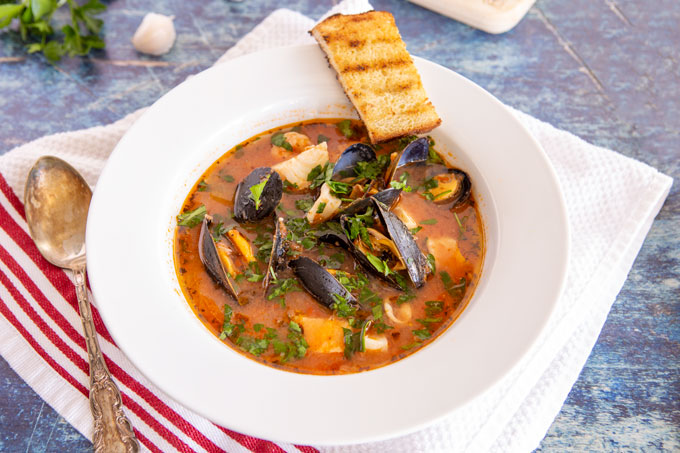 Plated bowl of cioppino with grilled sourdough crostini