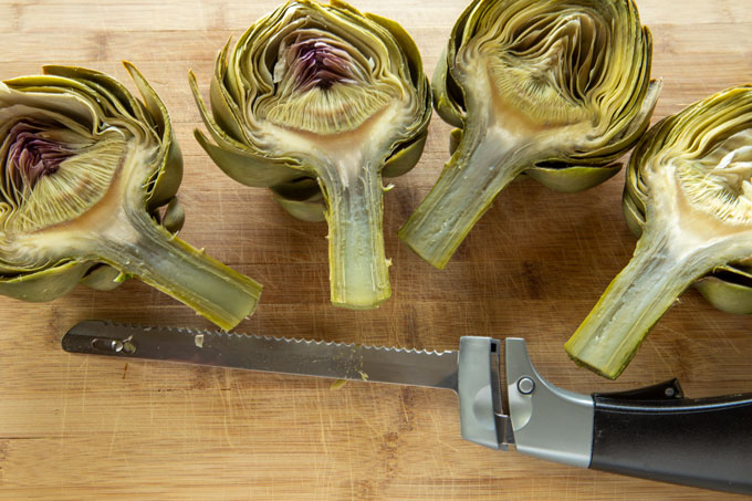 Cutting the artichoke in half with an electric knife