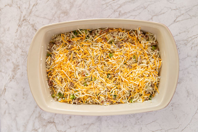 First layer of baking ingredients in the baking dish topped with half the shredded cheese