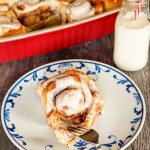 Feature shot of a cinnamon roll on a plate, being cut with a fork, and a milk bottle with a red and white straw