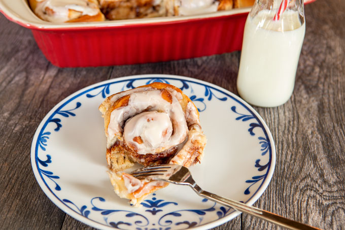 Cinnamon roll on a plate being cut with a fork
