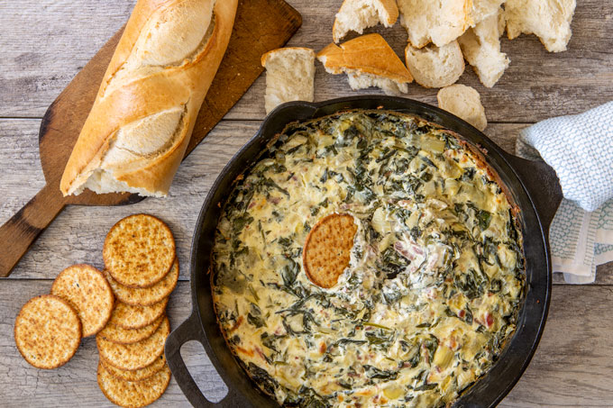 Baked artichoke, fresh spinach and bacon dip with a cracker dipped in the middle