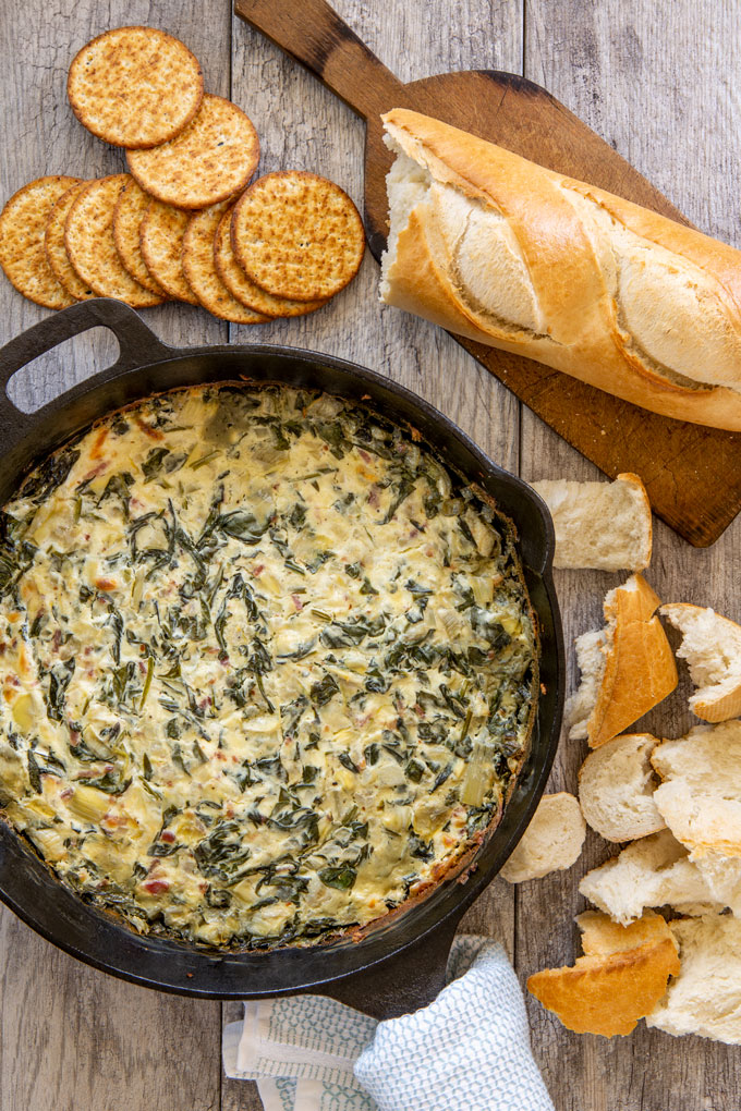 Baked artichoke, fresh spinach and bacon dip on a table with fresh bread and crackers