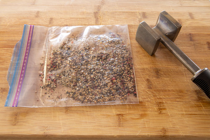 Cracking the peppercorns in a bag with a meat mallet