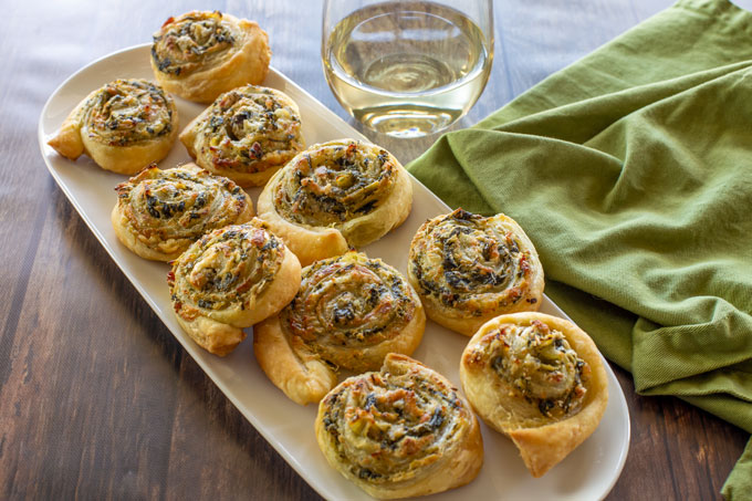 Baked spinach artichoke pinwheels on a serving platter with a napkin and a glass of wine