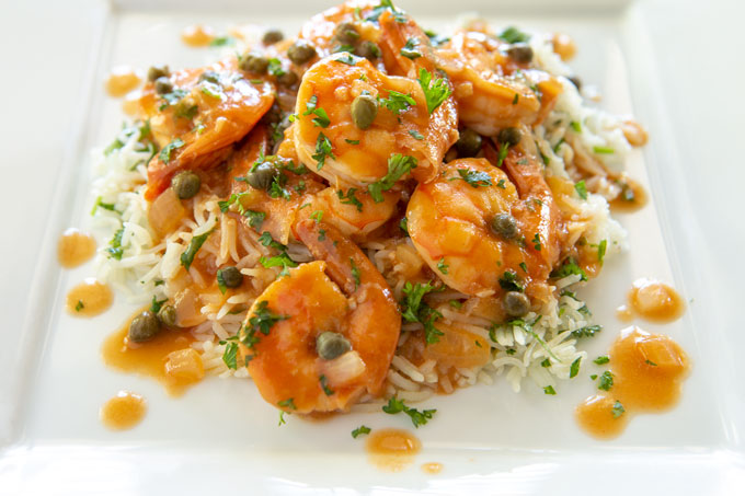 Shrimp and sauce plated over a bed of cilantro lime rice.