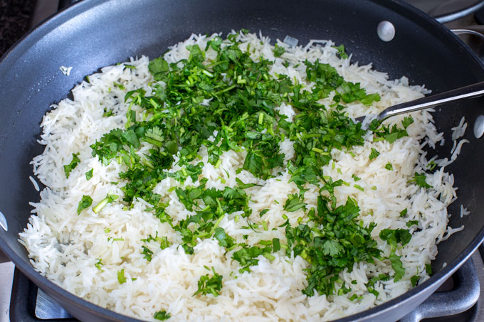 Adding cilantro and lime juice to cooked rice