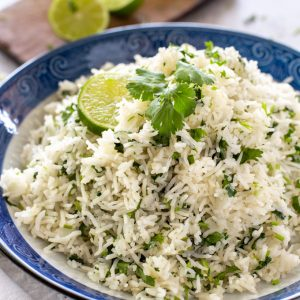 Cilantro Lime Rice in a bowl, garnished with lime and a cilantro section