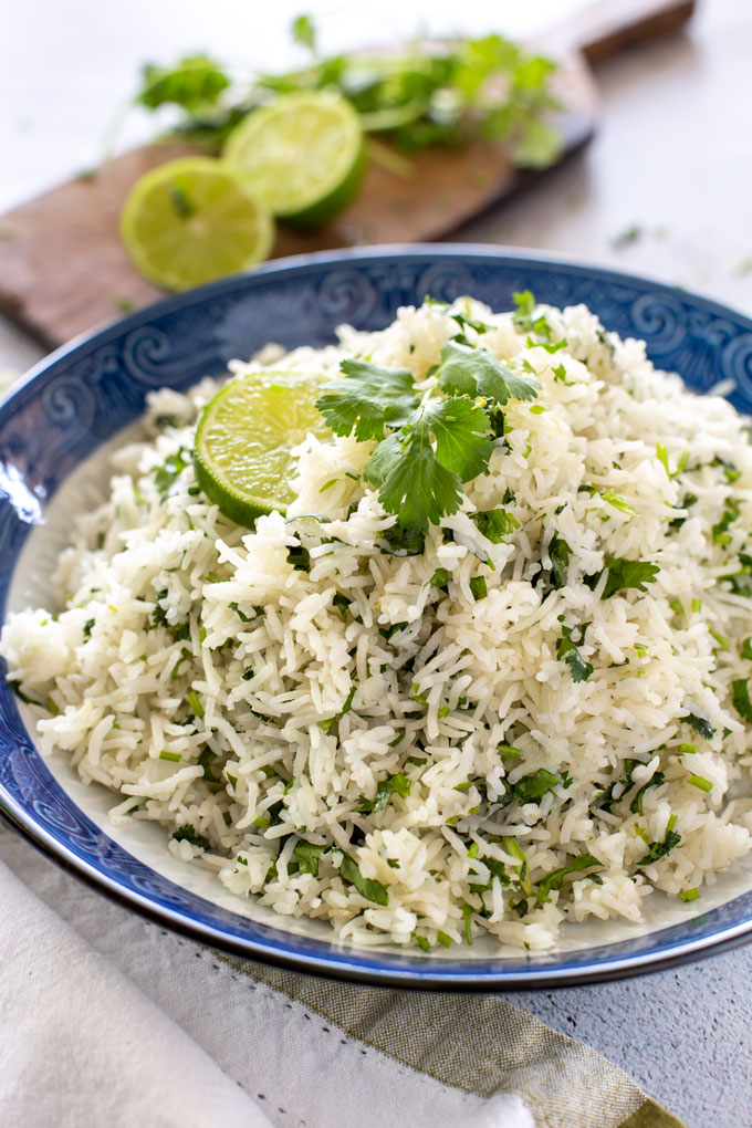 Portrait shot of Cilantro Lime Rice in a bowl, garnished with lime and a cilantro section